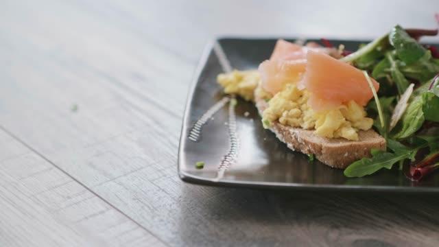 vídeos de stock, filmes e b-roll de salmão defumado com ovos mexidos com salada de verão - ovo mexido