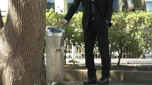 a smoker at park's smoking area, tokyo, japan - tobacco product stock videos & royalty-free footage
