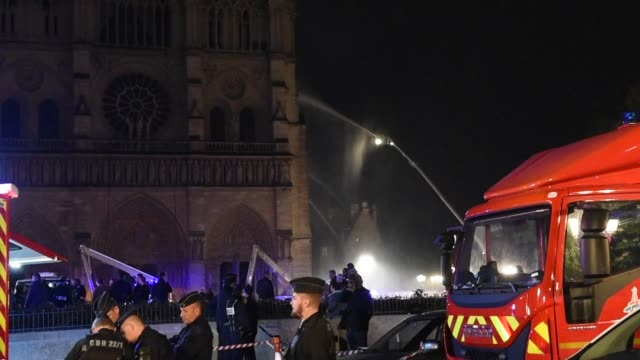 smokes and flames rise during a fire at notredame cathedral in central paris france on april 15 2019 a fire broke out at the landmark notredame... - gottesdienst stock-videos und b-roll-filmmaterial