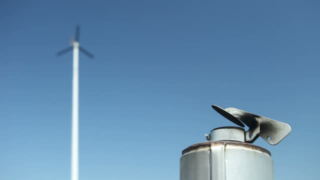 smokestack and wind turbine against a blue sky - diesel fuel stock videos and b-roll footage
