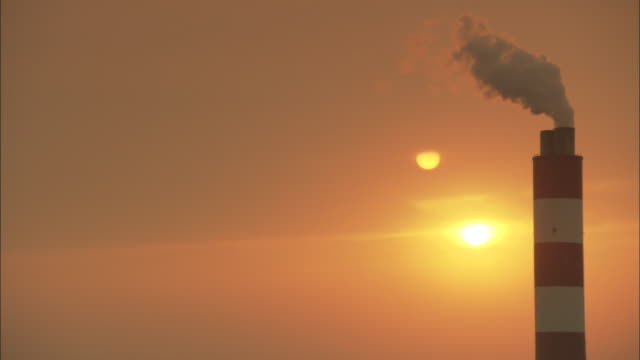 cu smokestack releasing smoke into sky with sun setting behind, huaneng yuhuan, yuhuan county, zhejiang, china - 工場の煙突点の映像素材/bロール