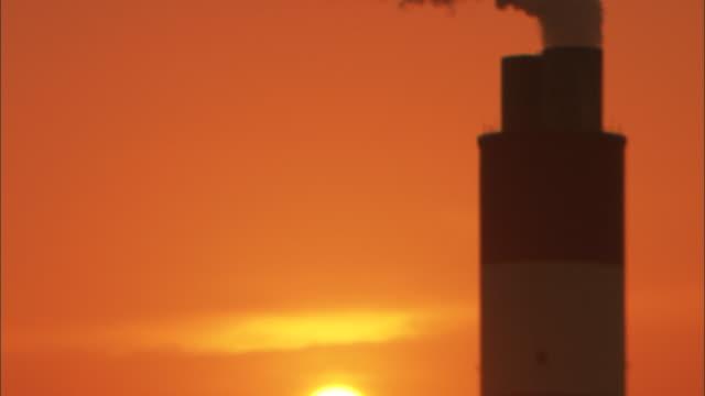 cu smokestack releasing smoke into sky with sun setting behind, huaneng yuhuan, yuhuan county, zhejiang, china - smoke stack stock videos & royalty-free footage
