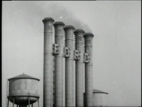 vidéos et rushes de smokestacks at a ford factory emit smoke. - 1910