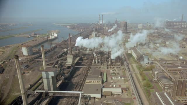 vídeos de stock e filmes b-roll de aerial smokestacks of factory / ijmuiden, noordzeekanaal, holland - cinematografia