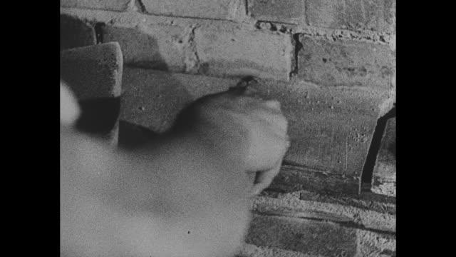 vídeos y material grabado en eventos de stock de smokestacks of uk factories / bricklayers construct wall in neighborhood / shovels move concrete into hole / men stack bricks on dolly / hand smooths... - paleta herramientas industriales