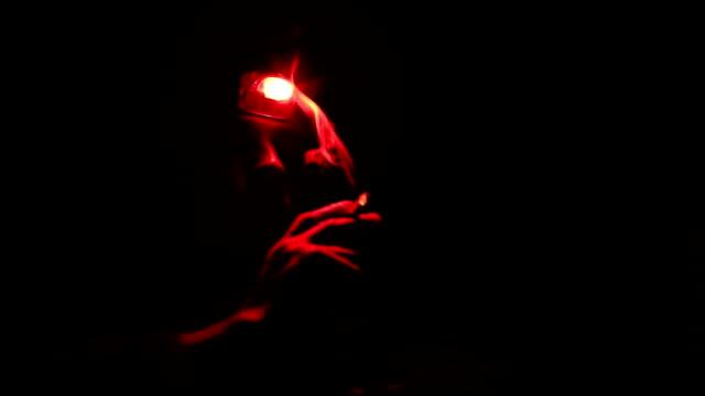 vídeos y material grabado en eventos de stock de fumar un cigarrillo en una rojo linterna sobre un paso negro de noche - linterna