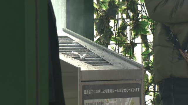 smoking area at park, tokyo, japan - aschenbecher stock-videos und b-roll-filmmaterial