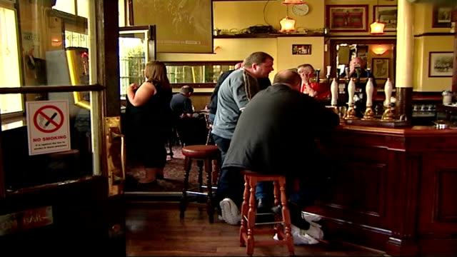 smoking ban in public places comes into effect; england: int people drinking in pug next sign 'it is against the law to smoke in these premises' 'no... - no smoking sign stock videos & royalty-free footage