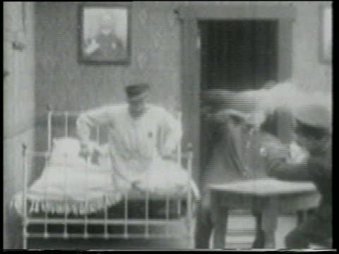 stockvideo's en b-roll-footage met b/w 1915 smoking cannonball exploding in room with relaxing keystone kops / short - dubbel bed