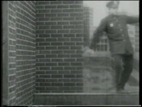stockvideo's en b-roll-footage met b/w 1915 smoking cannonball flying past keystone kop standing on building ledge / short - 1915