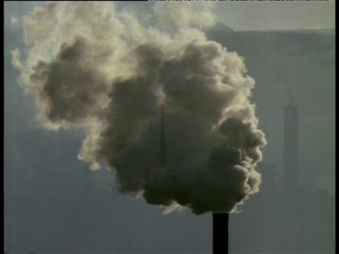 Smoking chimney superimposed on industrial landscape