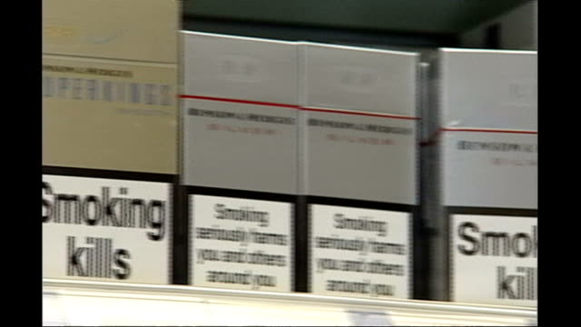 cigarette packets to display graphic images england int pan along cigarette packets on shelf with 'smoking kills' warning labels man smoking... - warning sign stock videos & royalty-free footage