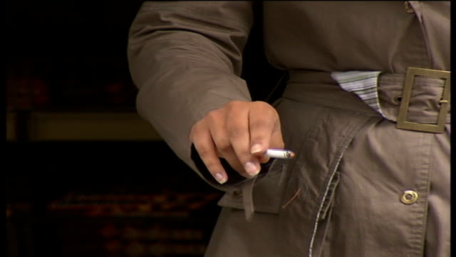 councils want powers to force companies to clear up cigarette butts left by workers; england: london: ext people smoking on the street cigarette... - sidewalk gutter stock videos & royalty-free footage