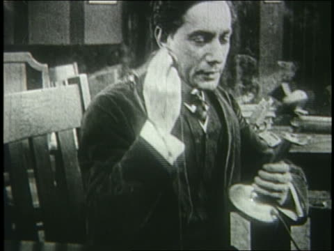 stockvideo's en b-roll-footage met b/w 1915 smoking man sitting at table talking on telephone / silent serial - 1915