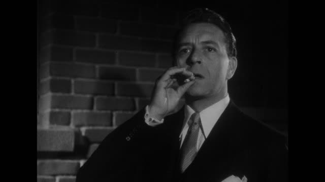 1948 smoking man watches woman enter her apartment building before following her - spy stock videos & royalty-free footage