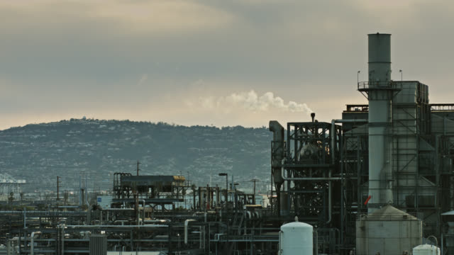 smoking oil refinery with suburban backdrop - industrial district stock videos & royalty-free footage