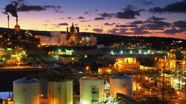smoking petrochemical plant at dusk - panning aerial - oil industry stock videos & royalty-free footage