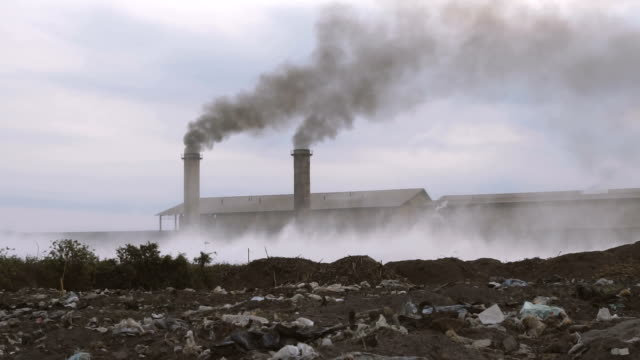 Smoking pipes of industrial factory and Fields garbage dump,the concept of environmental destruction