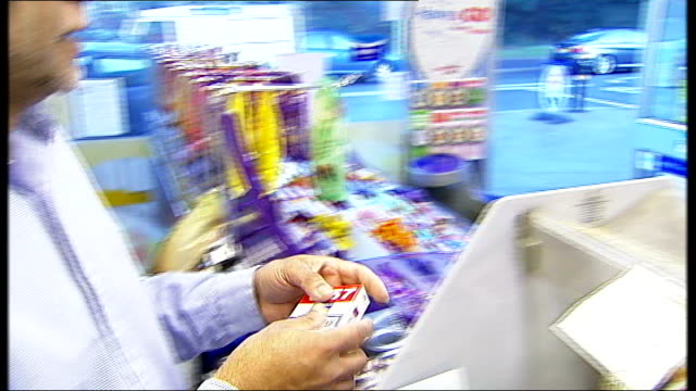 plans to ban cigarette displays in shops; woman buying packet of cigarettes in newsagent's shop cigarettes displayed on shelves in newsagent's - sachet stock videos & royalty-free footage