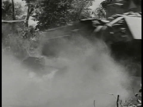 Smoking tank by side of road w/ Nationalist Chinese tank passing FG WS Nationalist Chinese soldier firing Bren machine gun propped on tree branch CU...