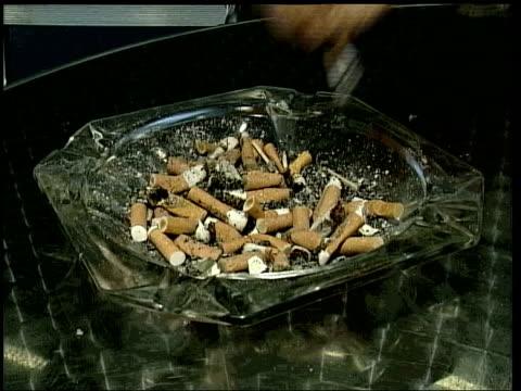 smoking vaccination news cigarette stubbed out - zigarettenstummel stock-videos und b-roll-filmmaterial