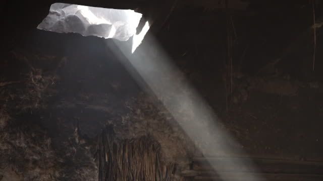 a smoky beam of light through a hole in the roof - hole stock videos & royalty-free footage