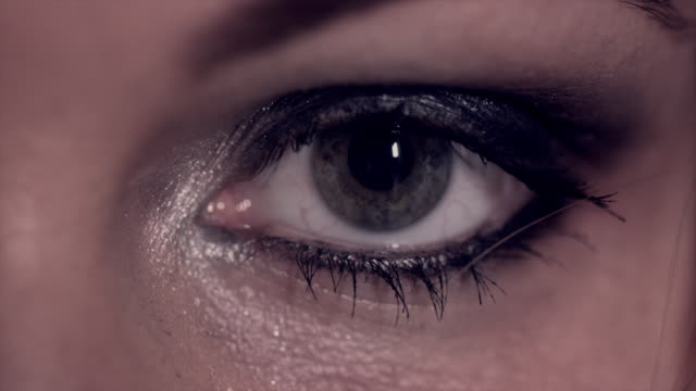 Smoky eye shadow covers the eyelid of a woman's eye as she opens it.