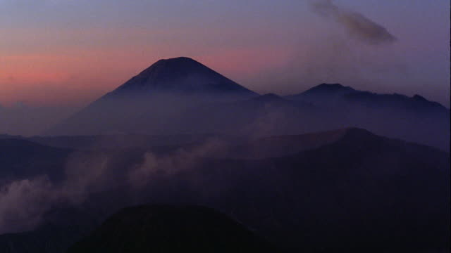 smoky landscape of volcanoes + mountains including mt. semeru + bromo crater / java, indonesia - bromo crater stock videos & royalty-free footage