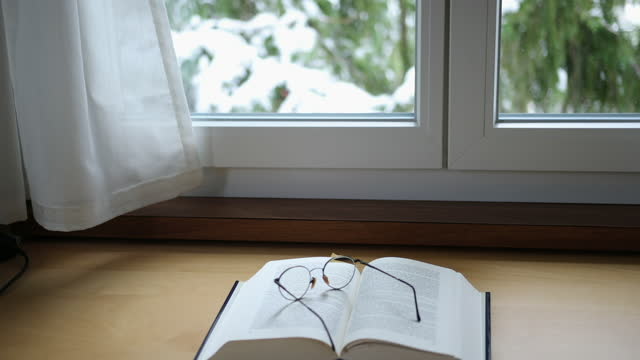 a smooth camera movement and focus rack beginning on a pair of glasses resting on an open book and then moving to reveal snow covered trees outside the window. - book stock videos & royalty-free footage