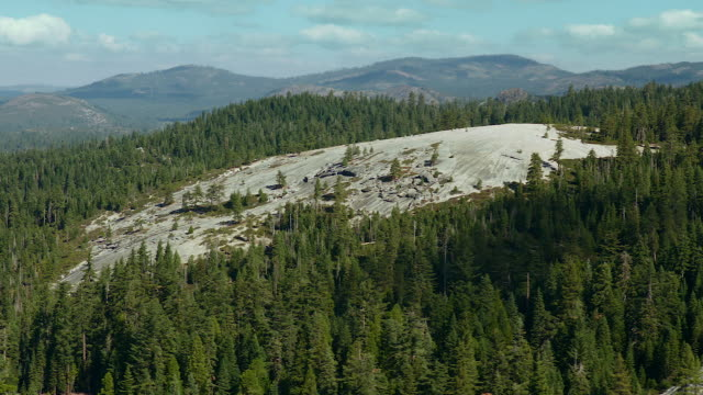 vidéos et rushes de smooth granite outcrop in california forest - outcrop