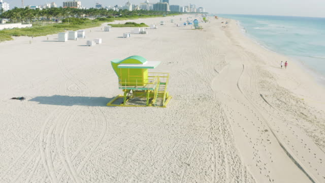 smooth high drone movement over miami beach colorful lifeguard in south beach, miami, florida at sunset - アールデコ地区点の映像素材/bロール