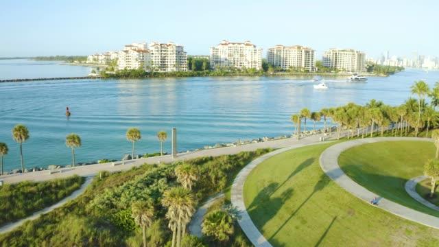 smooth high drone movement over miami canals, south beach, florida at sunrise - オーシャンドライブ点の映像素材/bロール