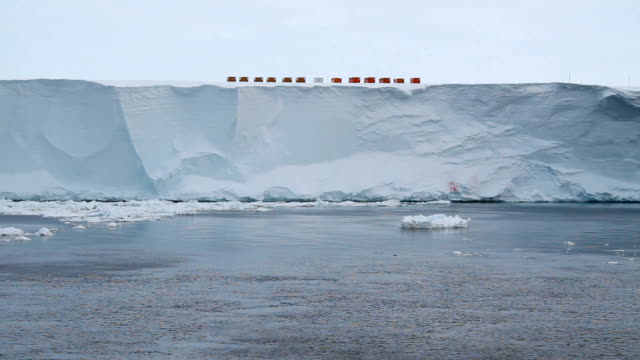 tracking smooth ice shelf with orange caravans on the peak, antarctica - camper trailer stock videos and b-roll footage
