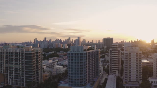 smooth upwards high drone movement over miami buildings in south beach, miami, florida at sunset - オーシャンドライブ点の映像素材/bロール