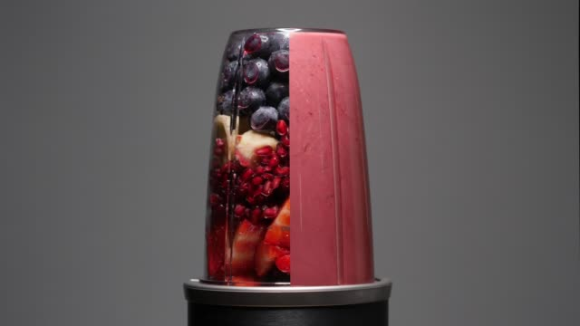 smoothie fruit drink being blended of summer fruits - smoothie stock videos & royalty-free footage