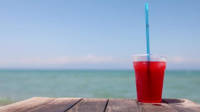 vídeos y material grabado en eventos de stock de smoothie en la mesa con hermosa playa y mar de fondo. concepto de vacaciones de verano - cóctel tropical
