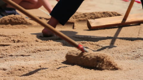 hd smoothing the sand for long jump - frau stock videos & royalty-free footage