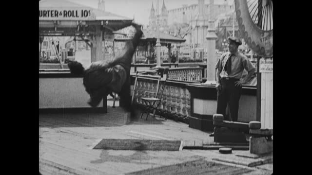 1917 Smug man kicks angry man (Buster Keaton) in the behind as he attempts to swing mallet and falls over