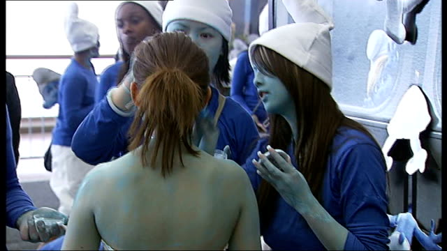 'smurfs' set new world record at the o2 arena; england: london: o2 arena: int crowd of people dressed as smurfs back view of woman having make-up... - itv london tonight weekend stock videos & royalty-free footage