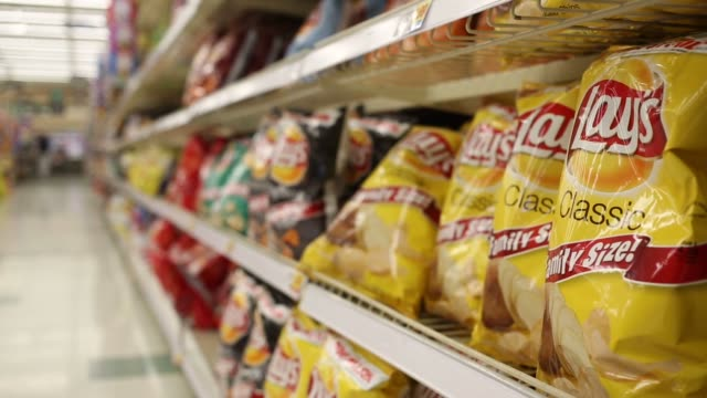snack chips manufactured by frito lay which is owned by pepsico are displayed for sale inside a kroger co grocery store in louisville kentucky us on... - unhealthy eating video stock e b–roll