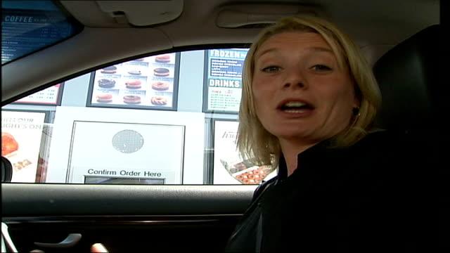 krispy kreme doughnuts arrive in uk; itn england: london: ext 'krispy kreme doughnuts drive-thru' sign tilt down car outside as order taken on... - 代理点の映像素材/bロール
