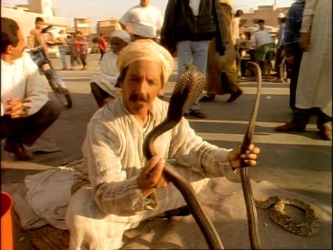 MS Snake charmer holding 2 cobras, Marrakesh marketplace, Morocco, Africa