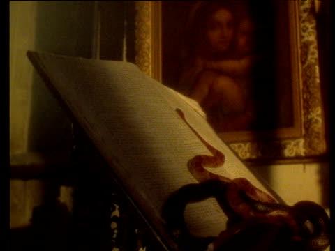 stockvideo's en b-roll-footage met snake slides up open bible on lectern - lessenaar