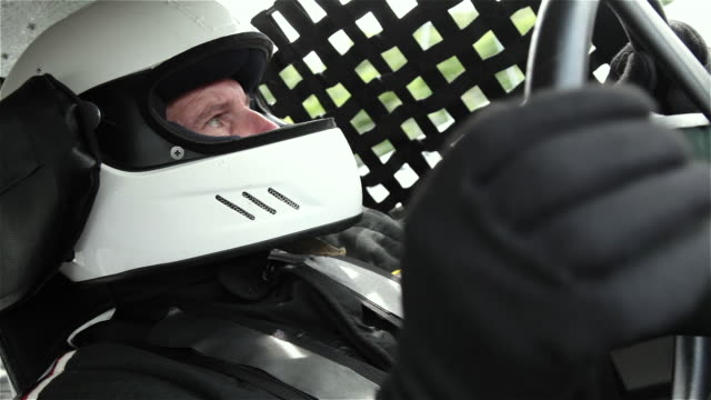ECU. Snap zoom on stock car driver in white helmet as he stares ahead in intense race.