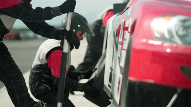 cu. snap zooms on experienced pit crew working together to jack stock car and replace tires on pit road. - pit stop stock videos & royalty-free footage