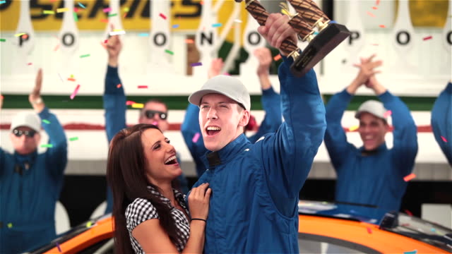 Snap zooms on young stock car driver holding up trophy and hugging beautiful woman as racing team celebrates.
