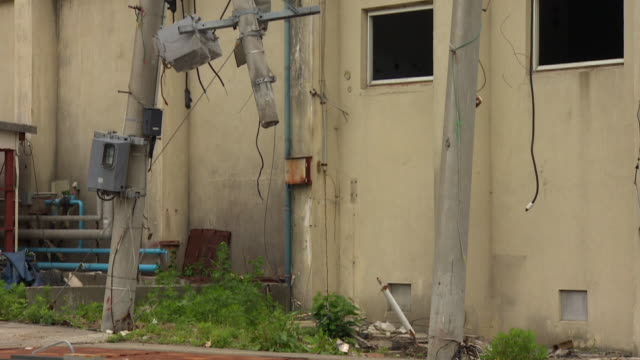 snapped power poles stand outside buildings devastated by an earthquake. - 地震点の映像素材/bロール