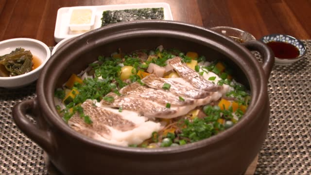 snapper fish on nutritious hot stone pot rice - setting the table stock videos & royalty-free footage