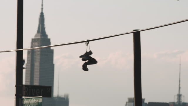Sneakers hang on a telephone lin with NYC's E,pire State Building in the background.