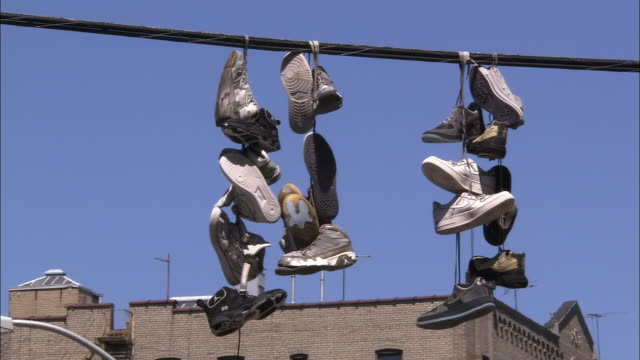 vídeos de stock e filmes b-roll de sneakers hanging from electrical wire - ténis calçado desportivo